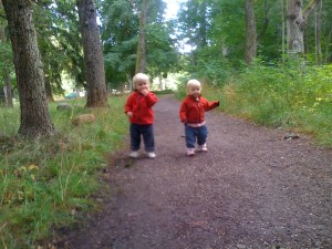 Matilda och Antonia på skogstig i röda jackor